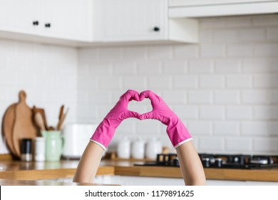 Heart made of pink protective gloves on white kitchen background.. Woman hands wearing protective gloves. Concept of clean kitchen, successful thumb up yes ok sign