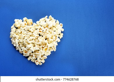 Heart made of popcorn on color background