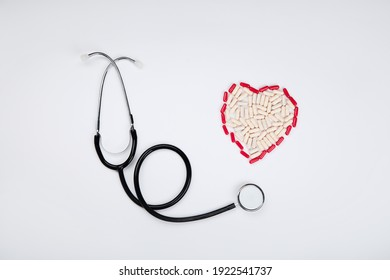 Heart made of red pills and stethoscope. Medicine and healthcare concept. Top view, Copy space