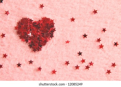 Heart made up of red stars arranged on pink fluffy background