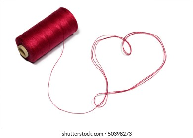 Heart made of red thread with spool.