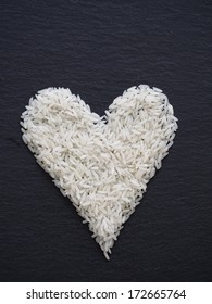 Heart made of rice on a black slate
