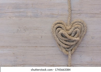 Heart made with rope on old wood.