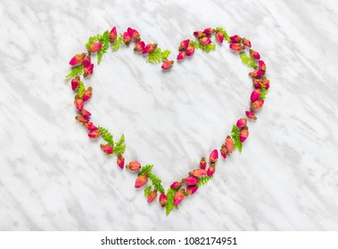 Heart made of rose buds and green leaves, on marble background.