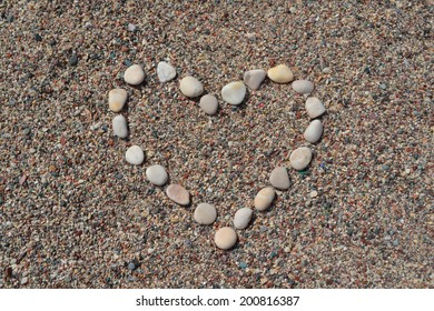 Heart made of stones on sand