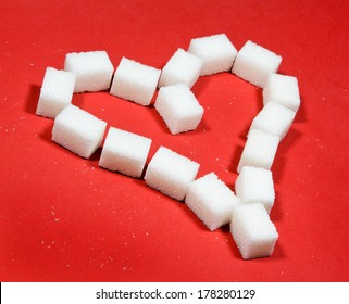 Heart made of sugar cubes on red background.