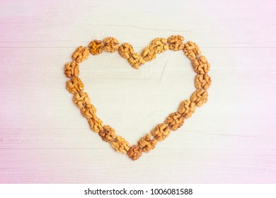 Heart made with walnuts on gray wooden background. Pile of walnuts forming a heart. Healthy eating concept. Walnuts are good fot your heart for energy. palpitation