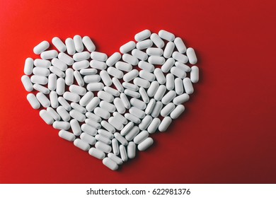 Heart made of white pills on red background, Heart disease medications, Drugs for Heart Disease