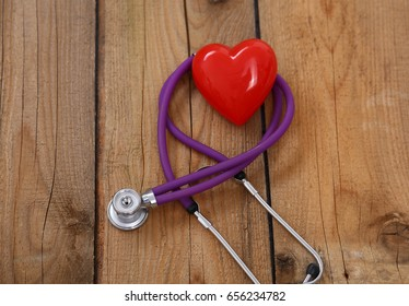 A heart with a medical stethoscope, isolated on wooden background, selective focus.