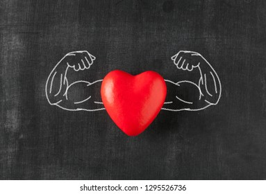 Heart with muscular arms drawn on blackboard
