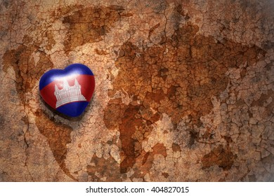 heart with national flag of cambodia on a vintage world map crack paper background. concept