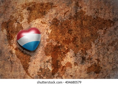 heart with national flag of luxembourg on a vintage world map crack paper background. concept