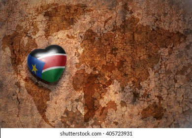 heart with national flag of south sudan on a vintage world map crack paper background. concept