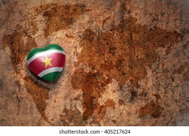 heart with national flag of suriname on a vintage world map crack paper background. concept