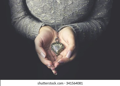 Heart necklace in woman hands