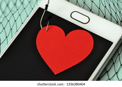 Heart on fish hook on mobile phone and fishing net - Love concept