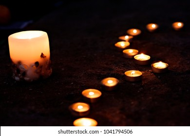 Heart on the sand of burning candles. Romance.