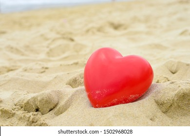 Heart on the sand on the summer beach with sea background. Close-up.
