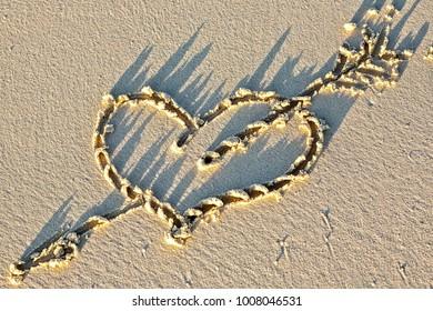 Heart on a sandy sunset beach