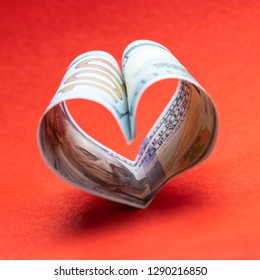 Heart from one hundred dollar bills USA. Red background. Concept of money and love and a gift for Valentine's Day. Square frame for instagram.