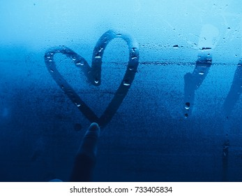 Heart paint by finger drawing on glass window in rainy day.