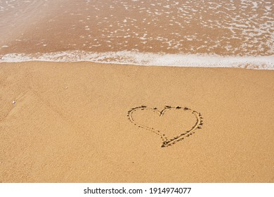 Heart painted on the sand on the beach and foam from the waves. Valentines day concept.