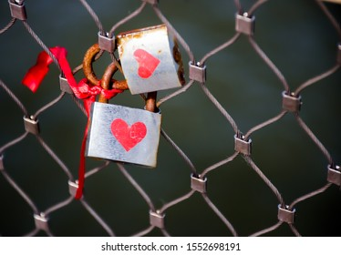 Heart painted silver colour locks on a bridge fence. Signs of love and loyalty. Valentines day concept. Postcard for lovers