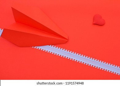 heart and paper airplane on red background
