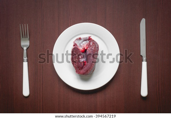 heart of a pig on a plate with knife and fork