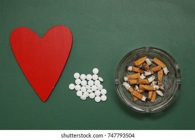 Heart and pills and cigarette butts on green wooden surface. To quit Smoking. The harm of Smoking