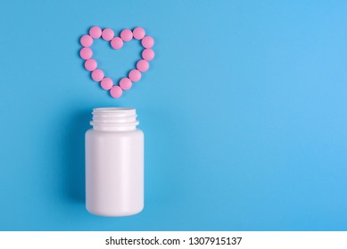 Heart of pink pills, tablets and white bottle on blue background. Copy space for text