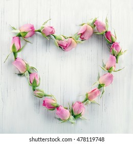 Heart of pink roses on white wooden background