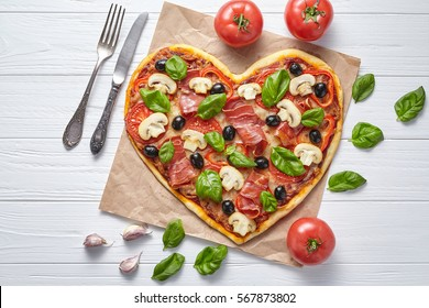 Heart pizza love concept Valentine's Day symbol romantic delicious dinner Italian homemade baked food. Prosciutto, olives, champignon mushrooms, basil and mozzarella meal served on white wooden table