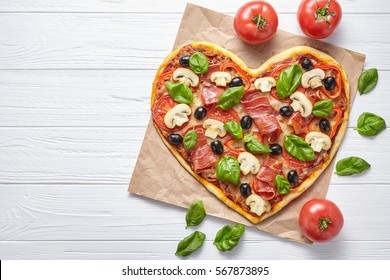 Heart pizza love concept Valentine's Day romantic dinner Italian baked food. Prosciutto, olives, champignon mushrooms, basil and mozzarella meal served on white wooden table