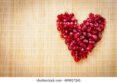 Heart of pomegranate on mat, love heart, fresh