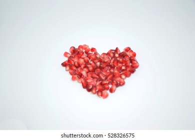 Heart of pomegranate seeds on withe background