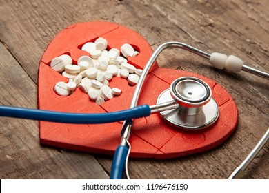 Heart puzzle red and white pills and a stethoscope on a wooden background background. Concept treatment of heart disease pills