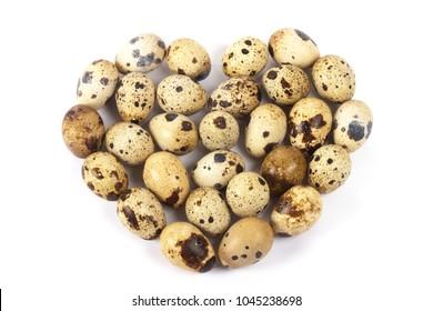 Heart of quail eggs on white background.