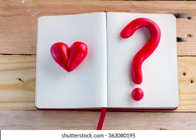 heart and question mark red symbol on notebook on wooden floor :love concept