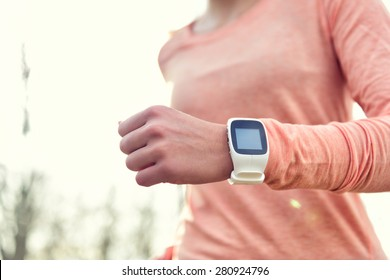 Heart rate monitor smart watch for sport. Athlete wearing heart rate monitor. Runner using sports smartwatch on running workout outside. Female athlete tracking activities using wearable technology.