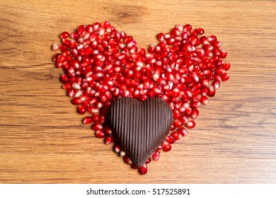 Heart of red pomegranate seeds and dark chocolate - a declaration of love on Valentine's Day.