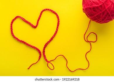 Ein Herz aus rotem Faden auf gelbem Hintergrund