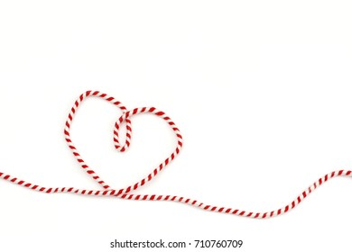 heart from red white ribbon on white