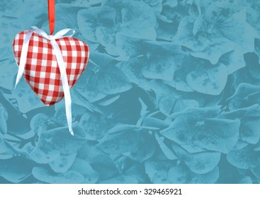 Heart with ribbon against a blue textured background, with room for text. The heart is made of fabric with a red and white (gingham) checked pattern. The flowers used for the texture are hydrangea.