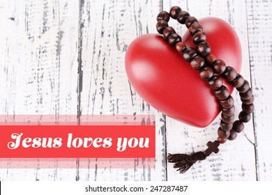 Heart with rosary beads on wooden background and text Jesus loves you