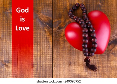 Heart with rosary beads on wooden background and text God is Love