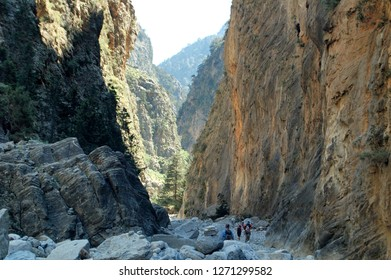 In the heart of the Samaria Gorge between Agia ROumeli and Omalos (Crete, Chora Sfakion, Greece) during a hike on the GR E4. Group of hiker evolving in imense gorges in orange color.
