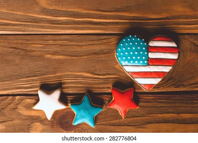 Heart shape american flag with patriotic ginfer stars for the 4th of July on the wooden background
