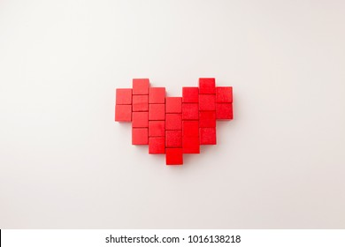 heart shape from array red block toy on white paper background with copy space