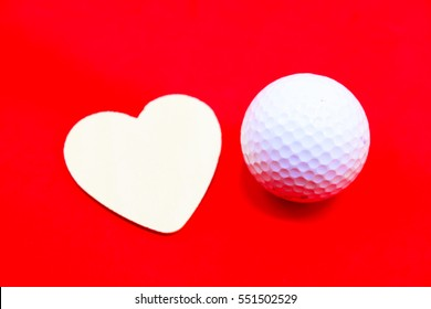 Heart shape and ball are on red background.